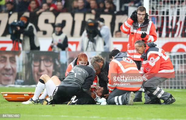 Christian Gentnerof Stuttgart is being treated after a heavy foul on him by Koen Casteels of Wolfsburg during the Bundesliga match between VfB...