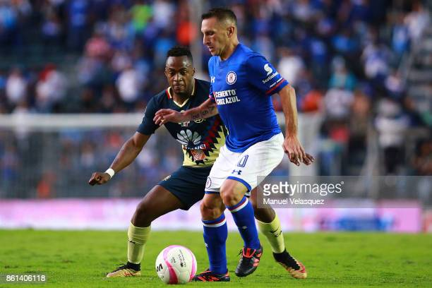 Christian Gimenez of Cruz Azul struggles for the ball against Alex Ibarra of America during the 13th round match between Cruz Azul and America as...