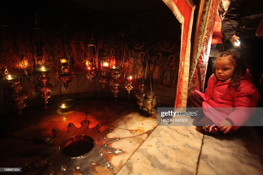 A Christian girl sits near the Altar of the Nativity, believed to be the place where the Virgin Mary gave birth to Jesus Christ, inside the Grotto at the Church of the Nativity in the biblical West Bank city of Bethlehem, on December 24, 2012. Thousands of Palestinians and tourists were flocking to Bethlehem to mark Christmas at the site where many believe Jesus Christ was born.