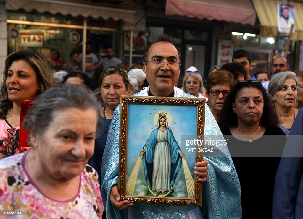 A Christian Greek Catholic (also known as Melkite) priest carries a picture of Virgin Mary during a procession marking the month of Virgin Mary in the Beirut Christian dominated neighbourhood of Ashrafiyeh on May 30, 2016. / AFP / PATRICK BAZ