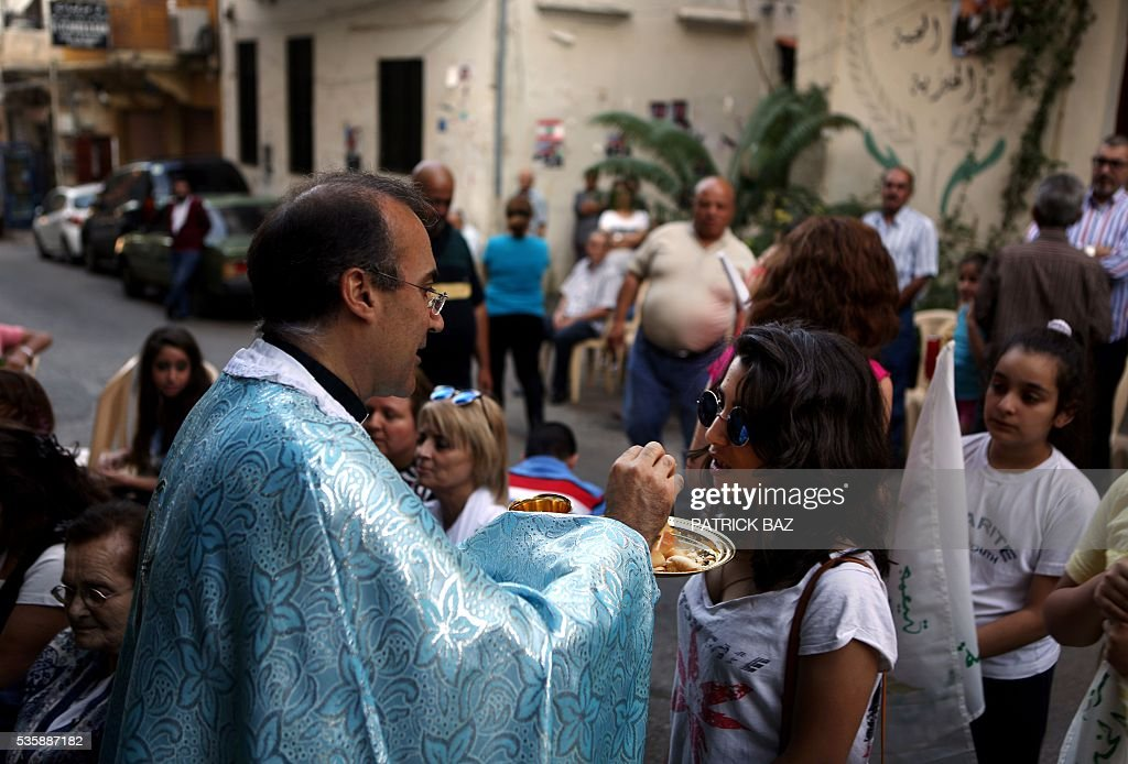 A Christian Greek Catholic (also known as Melkite) priest gives the communion to Lebanese Christians prior to a procession marking the month of Virgin Mary in the streets of the Beirut Christian dominated neighbourhood of Ashrafiyeh on May 30, 2016. / AFP / PATRICK BAZ