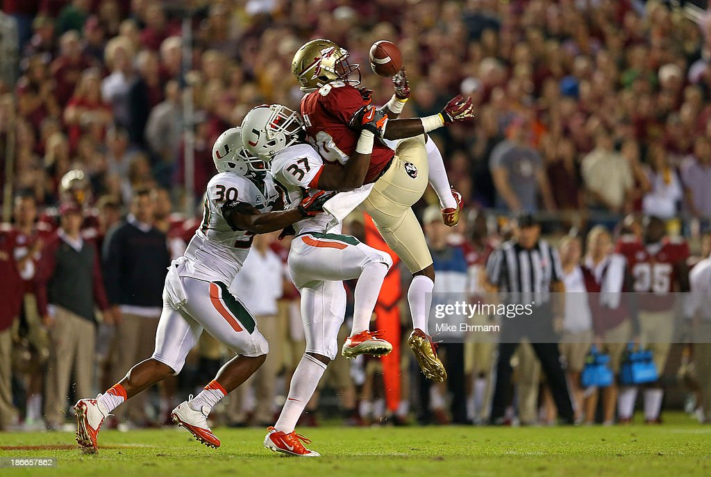 Christian Green #89 of the Florida State Seminoles misses a catch defended by Ladarius Gunter #37 and A.J. Highsmith #30 of the Miami Hurricanes during a game at Doak Campbell Stadium on November 2, 2013 in Tallahassee, Florida.