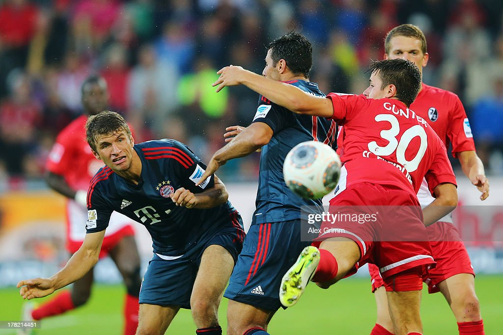 Christian Guenter of Freiburg is challenged by <a gi-track='captionPersonalityLinkClicked' href=/galleries/search?phrase=Claudio+Pizarro&family=editorial&specificpeople=217807 ng-click='$event.stopPropagation()'>Claudio Pizarro</a> and <a gi-track='captionPersonalityLinkClicked' href=/galleries/search?phrase=Thomas+Mueller&family=editorial&specificpeople=5842906 ng-click='$event.stopPropagation()'>Thomas Mueller</a> (R-L) of Muenchen during the Bundesliga match between SC Freiburg and FC Bayern Muenchen at MAGE SOLAR Stadium on August 27, 2013 in Freiburg im Breisgau, Germany.