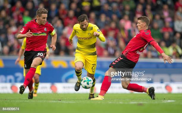 Christian Guenther and Mike Frantz of Freiburg and Gonzalo Castro of Dortmund fight for the ball during the Bundesliga match between SportClub...