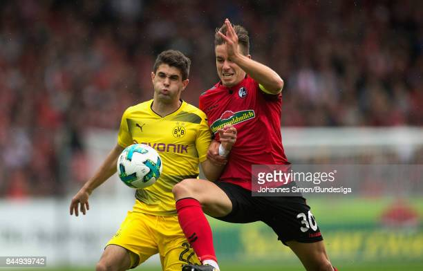 Christian Guenther of Freiburg and Christian Pulisic of Dortmund fight for the ball during the Bundesliga match between SportClub Freiburg and...