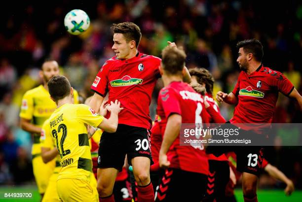 Christian Guenther of Freiburg and Christian Pulisic of Dortmund head for the ball during the Bundesliga match between SportClub Freiburg and...