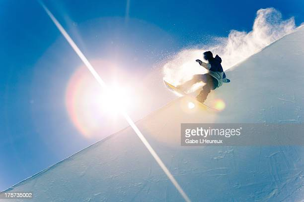 Christian Haller slashes a half pipe wall in front of the sun on August 18 2011 in Snowpark New Zealand