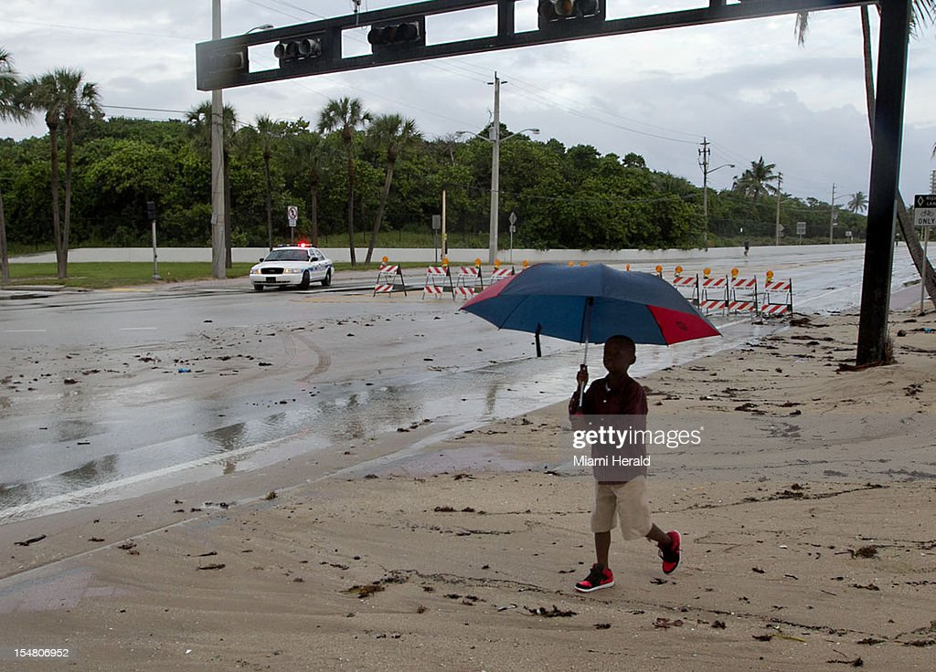 Christian Hamilton, 6, walks across a closed A1A at Sunrise Blvd. High tides and wind driven waves closed the road on Ft. Lauderdale Beach, Florida, Friday, October 26, 2012.