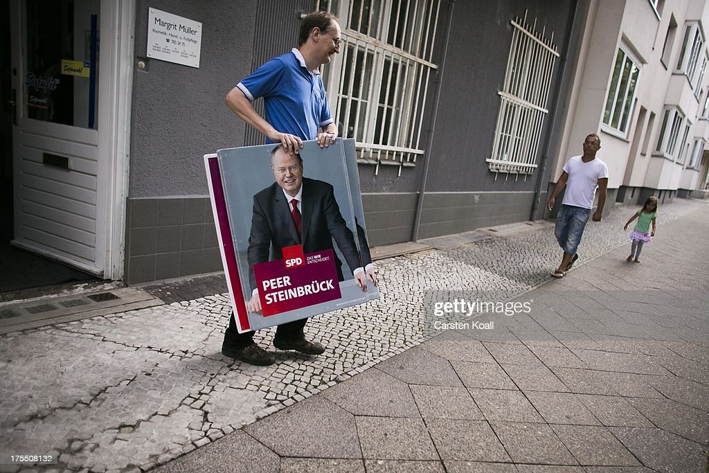 SPD- Christian Heidler, SPD-Member since 1980, carries an election campaign poster showing German Social Democrats (SPD) chancellor candidate Peer Steinbrueck on August 4, 2013 in Berlin, Germany. Germany is scheduled to hold federal elections on September 22 and so far current Chancellor Angela Merkel and her party, the German Christian Democrats (CDU), have a strong lead over the opposition.