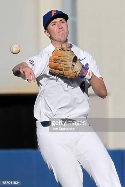 Christian Hicks of the Gators makes the throw over to first base before the college baseball game between the Florida State Seminoles and the Florida...