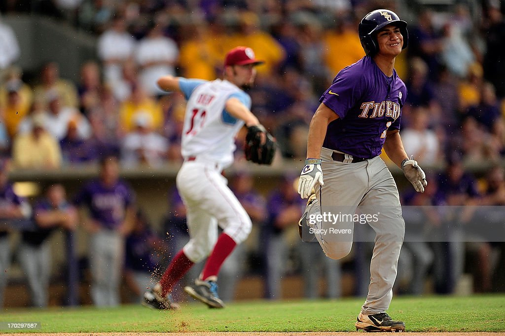 Christian Ibarra #14 of the LSU Tigers tries to beat a throw by Dillon Overton #13 of the Oklahoma Sooners during Game 2 of the NCAA baseball Super Regionals at Alex Box Stadium on June 8, 2013 in Baton Rouge, Louisiana.