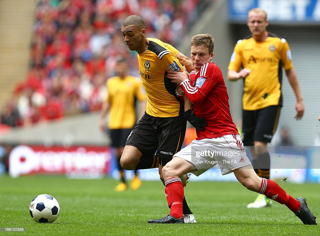 Christian Jolley of Newport County battles with Jay Harris of Wrexham during the Blue Square Bet Premier Conference play-off final match between Wrexham and Newport County at Wembley Stadium on May 5, 2013 in London, England.