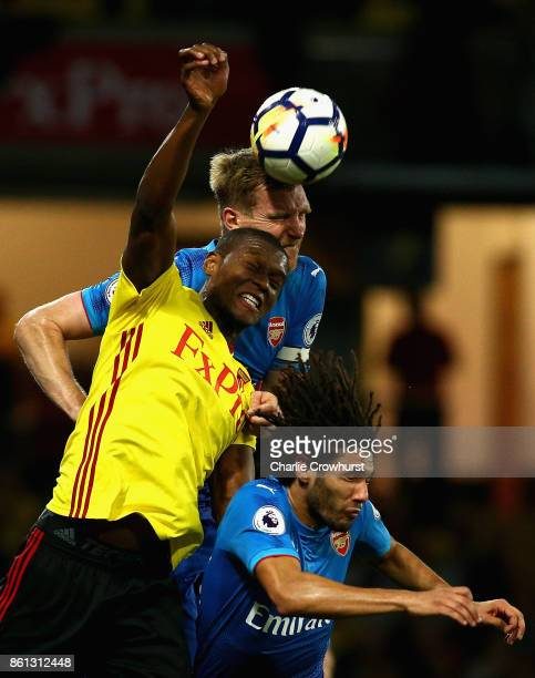 Christian Kabasele of Watford jumps between Per Mertesacker and Mohamed Elneny of Arsenal during the Premier League match between Watford and Arsenal...