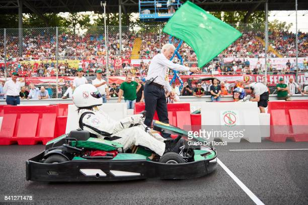 Christian Karembeu of France watches FIA Race Director Charlie Whiting wave the starting flag of the Heineken Champions of the Grid gokart race ahead...