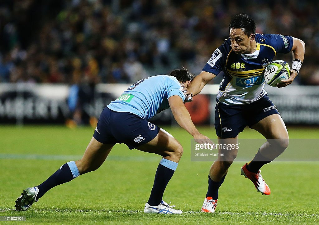 Christian Lealiifano of the Brumbies fends off a tackle during the round 12 Super Rugby match between the Brumbies and the Waratahs at GIO Stadium on...
