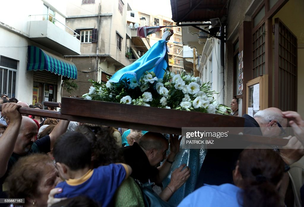 Christian Lebanese carry a statue of Virgin Mary during a procession marking the month of Virgin Mary in a Beirut Christian dominated neighbourhood on May 30, 2016. / AFP / PATRICK BAZ