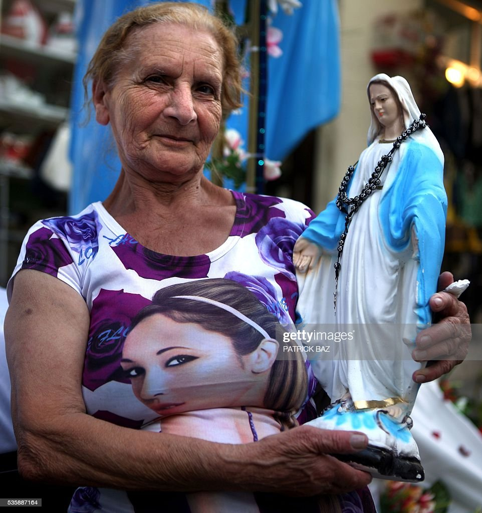 A Christian Lebanese woman holds a statue of Virgin Mary during a procession marking the month of Virgin Mary in a Beirut Christian dominated neighbourhood on May 30, 2016. / AFP / PATRICK BAZ