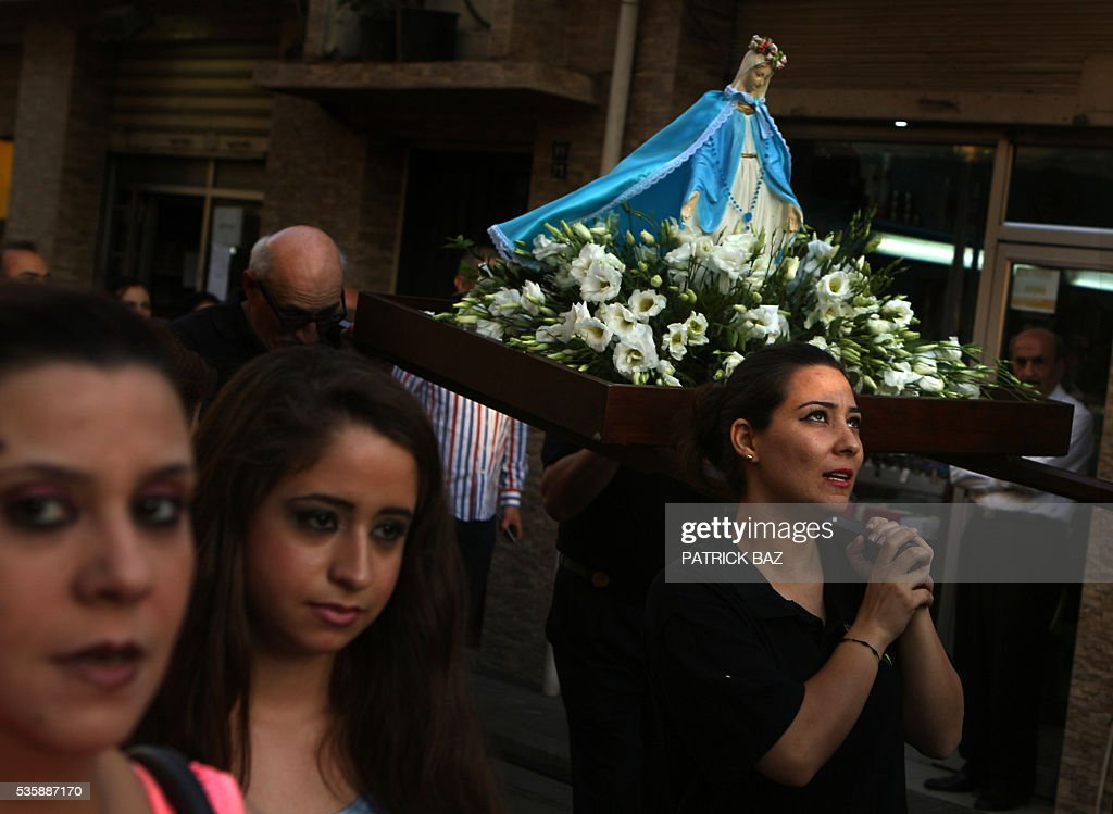 Christian Lebanese women carry a statue of Virgin Mary during a procession marking the month of Virgin Mary in a Beirut Christian dominated neighbourhood on May 30, 2016. / AFP / PATRICK BAZ