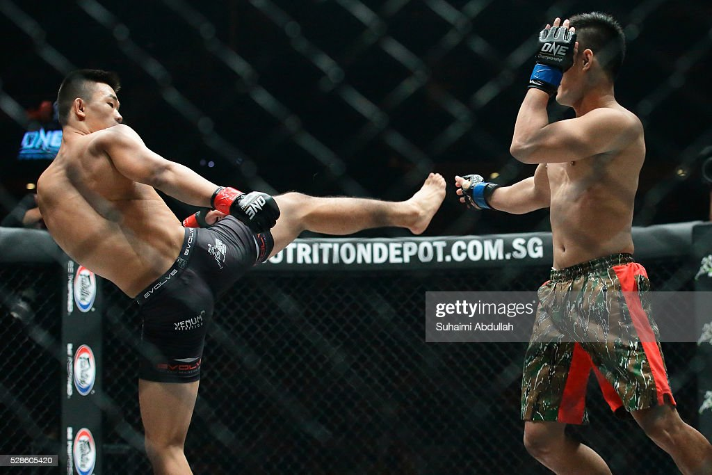 Christian Lee (L) of Singapore fights Cary Bullos of Philippines in the featherweight bout during One Championship: Ascent to Power at Singapore Indoor Stadium on May 6, 2016 in Singapore.