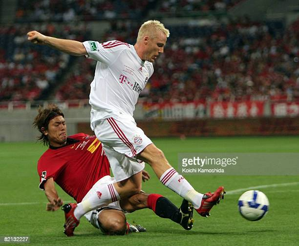 Christian Lell of Bayern Munich challenges for the ball with Takahito Soma of Urawa Red Diamonds during the pre season friendly between Urawa Red...