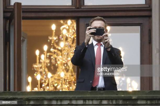 Christian Lindner chairman of Germany's free democratic FDP party takes a picture of the the waiting press from the balcony during a break of...