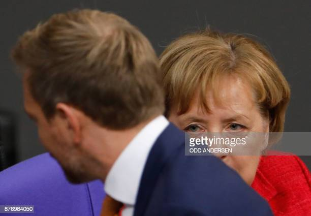 Christian Lindner leader of the free democratic FDP party walks past German Chancellor Angela Merkel during a session at the Bundestag on November 21...