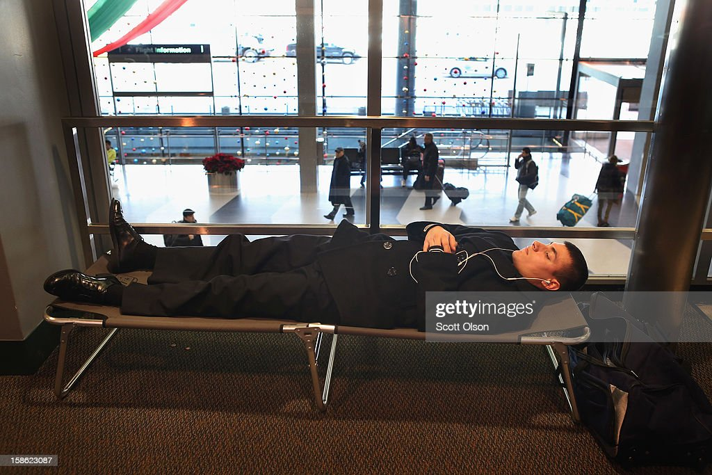 Christian Lopez gets some rest on a cot in the hallway outside the USO as he waits to catch a flight home to San Antonio at O'Hare International Airport on December 21, 2012 in Chicago, Illinois. Today is the busiest air travel day of the Christmas holiday, with an estimated 200,000 travelers expected to travel through O'Hare today.