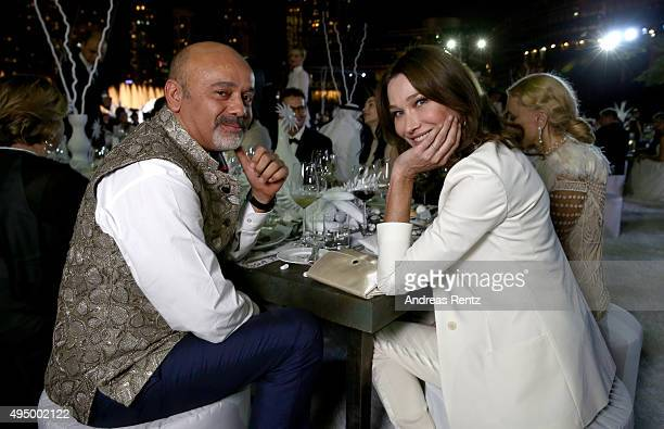 Christian Louboutin and Carla Bruni attend the Gala event during the Vogue Fashion Dubai Experience 2015 at Armani Hotel Dubai on October 30 2015 in...