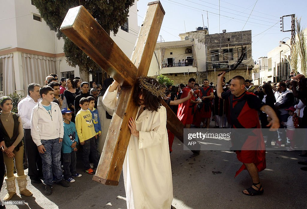 A Christian man holds a large wooden cross as Lebanese Christians reenact the crucifixion of Jesus Christ during the Good Friday procession in the southern village of Qraiyeh on March 29, 2013. Christians around the world are marking the Holy Week, commemorating the crucifixion of Jesus Christ, leading up to his resurrection on Easter.