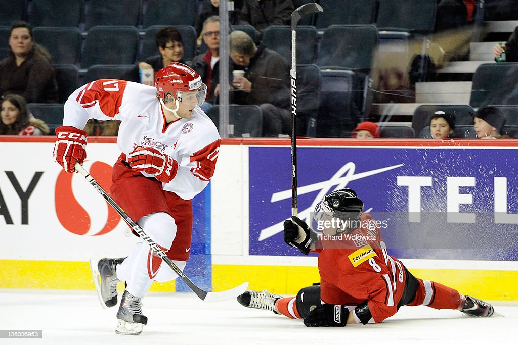 Christian Marti #8 of Team Switzerland falls to the ice in front of Nicklas Jensen #17 of Team Denmark during the 2012 World Junior Hockey Championship game at the Saddledome on January 2, 2012 in Calgary, Alberta, Canada.