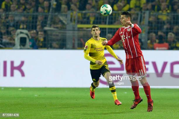 Christian Mate Pulisic of Dortmund and James Rodriguez of Bayern Muenchen battle for the ball during the German Bundesliga match between Borussia...