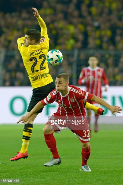 Christian Mate Pulisic of Dortmund and Joshua Kimmich of Bayern Muenchen battle for the ball during the German Bundesliga match between Borussia...
