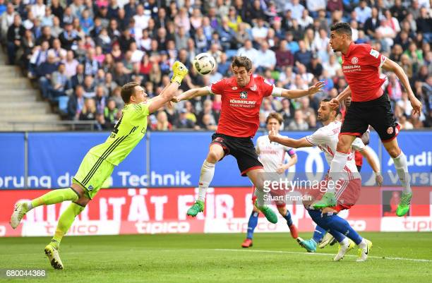 Christian Mathenia of Hamburg makes a save from Stefan Bell of Mainz during the Bundesliga match between Hamburger SV and 1 FSV Mainz 05 at...