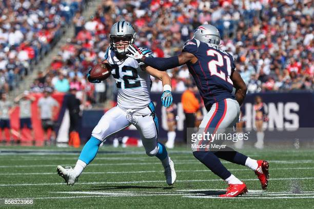 Christian McCaffrey of the Carolina Panthers runs with the ball against Malcolm Butler of the New England Patriots during the first half at Gillette...