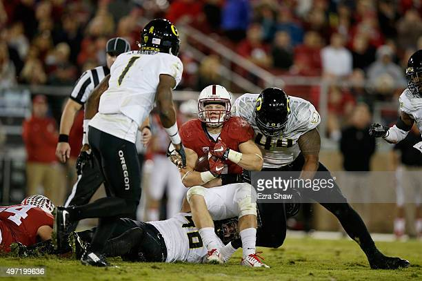 Christian McCaffrey of the Stanford Cardinal is tackled by DeForest Buckner of the Oregon Ducks at Stanford Stadium on November 14 2015 in Palo Alto...
