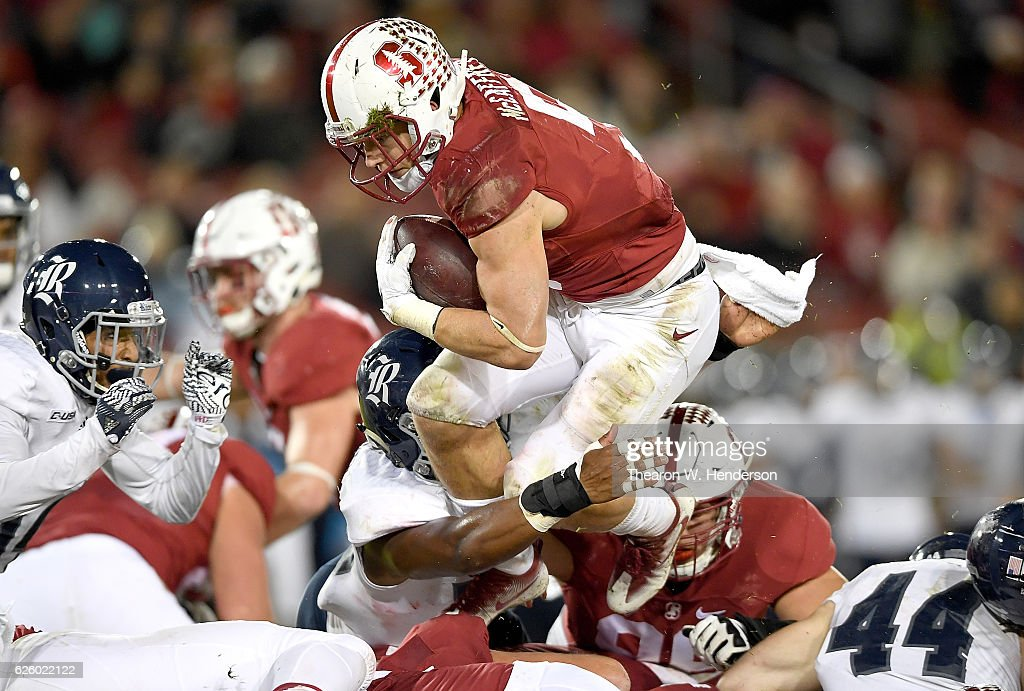 Christian McCaffrey #5 of the Stanford Cardinal leaps over the line for a three yard gain and a first down against the Rice Owls in the first quarter of their NCAA football game at Stanford Stadium on November 26, 2016 in Palo Alto, California.