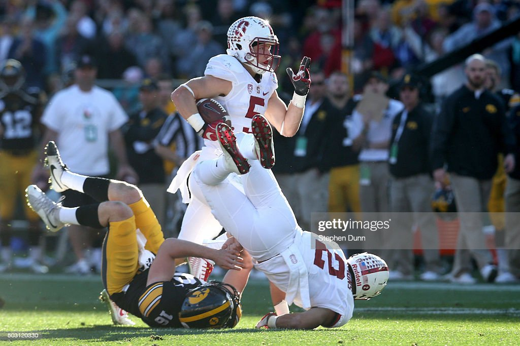 Christian McCaffrey of the Stanford Cardinal returns a punt for a touchdown past punter Dillon Kidd of the Iowa Hawkeyes who was tackled by Trenton...