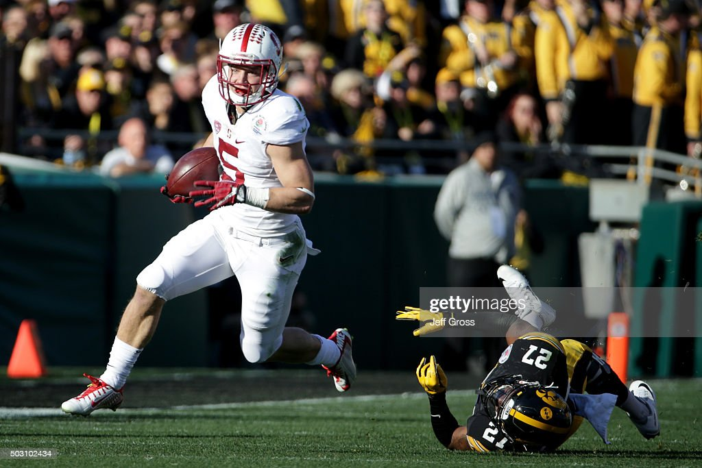 Christian McCaffrey of the Stanford Cardinal runs past Jordan Lomax of the Iowa Hawkeyes in the first quarter of the 102nd Rose Bowl Game on January...