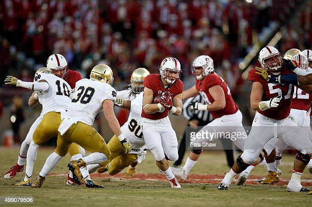 Christian McCaffrey of the Stanford Cardinal runs with the ball against the Notre Dame Fighting Irish at Stanford Stadium on November 28 2015 in Palo...