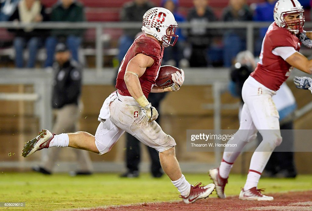 Christian McCaffrey #5 of the Stanford Cardinal scores on a nineteen yard touchdown run against the Rice Owls in the third quarter of their NCAA football game at Stanford Stadium on November 26, 2016 in Palo Alto, California.
