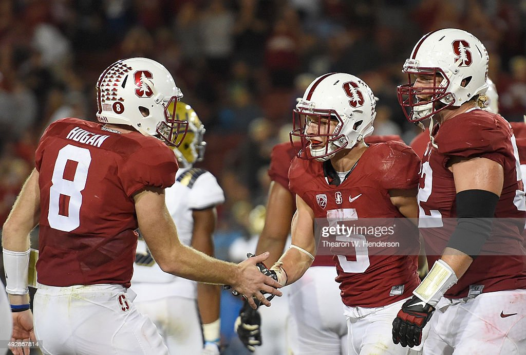 Christian McCaffrey #5 of the Stanford Cardinal's is congratulated by Kevin Hogan #8 and Graham Shuler #52 after McCaffrey scored his third touchdown of the game against the UCLA Bruins in the third quarter of an NCAA football game at Stanford Stadium on October 15, 2015 in Stanford, California.