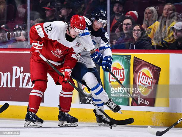 Christian Mieritz of Team Denmark battles for the puck with Janne Kuokkanen of Team Finland during the IIHF World Junior Championship preliminary...