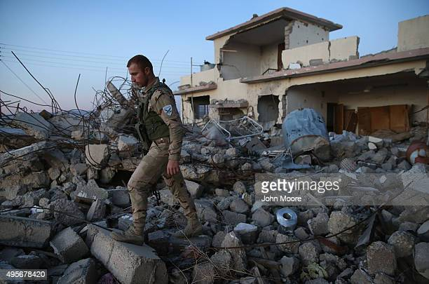 Christian militiaman walks over rubble from a US airstrike on November 4 2015 near the frontline with ISIS fighters in Telskuf northern Iraq All of...
