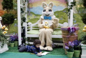 Christian Milutinovic colors on the floor while warming up to Patrick Huetten in the bunny suit during his 25 hour shift as the Easter Bunny at the...