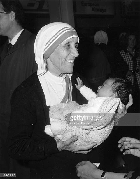 Christian missionary Mother Teresa of Calcutta holding a baby at Heathrow Airport London