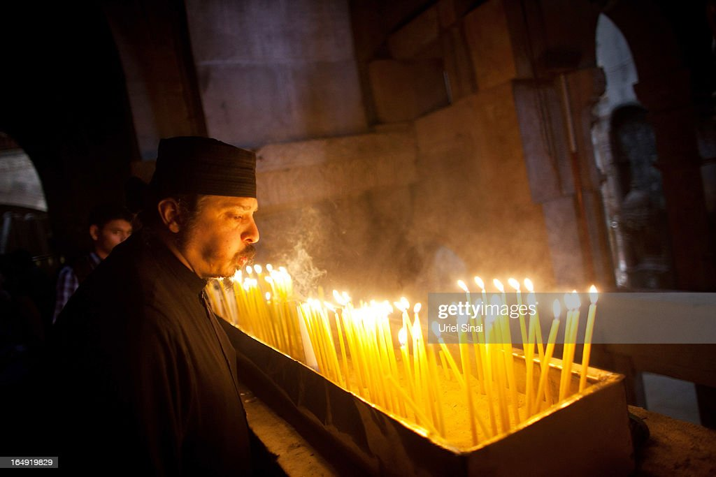 A Christian monk blows out candles to make room for more at the Church of the Holy Sepulchre during the Good Friday on March 29, 2013 in Jerusalem's Old City, Israel. Good Friday is celebrated by Christians throughout the world as the day Christ was crucified on the cross in the lead up to his resurrection on Easter.