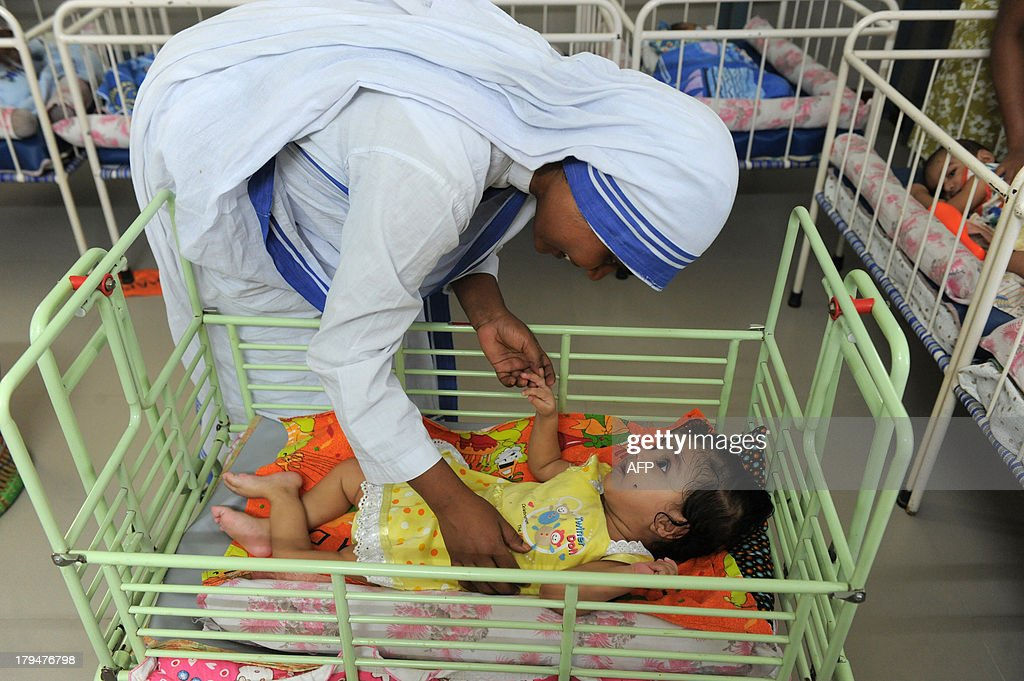 A Christian nun plays with an orphan at Shishu Bhavan, orphanage for discarded babies run by The Missionaries of Charity, on the eve of Mother Teresa's Death Anniversary in Ahmedabad on September 4, 2013. Mother Teresa, the founder of the Missionaries of Charity died on September 5, 1997. Currently, Shishu Bhavan has some 23 orphans looked after by the Christian nuns and their helpers. AFP PHOTO / Sam PANTHAKY