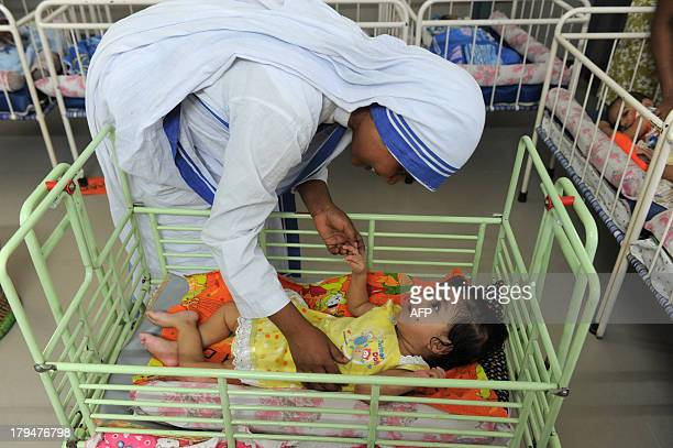 A Christian nun plays with an orphan at Shishu Bhavan orphanage for discarded babies run by The Missionaries of Charity on the eve of Mother Teresa's...