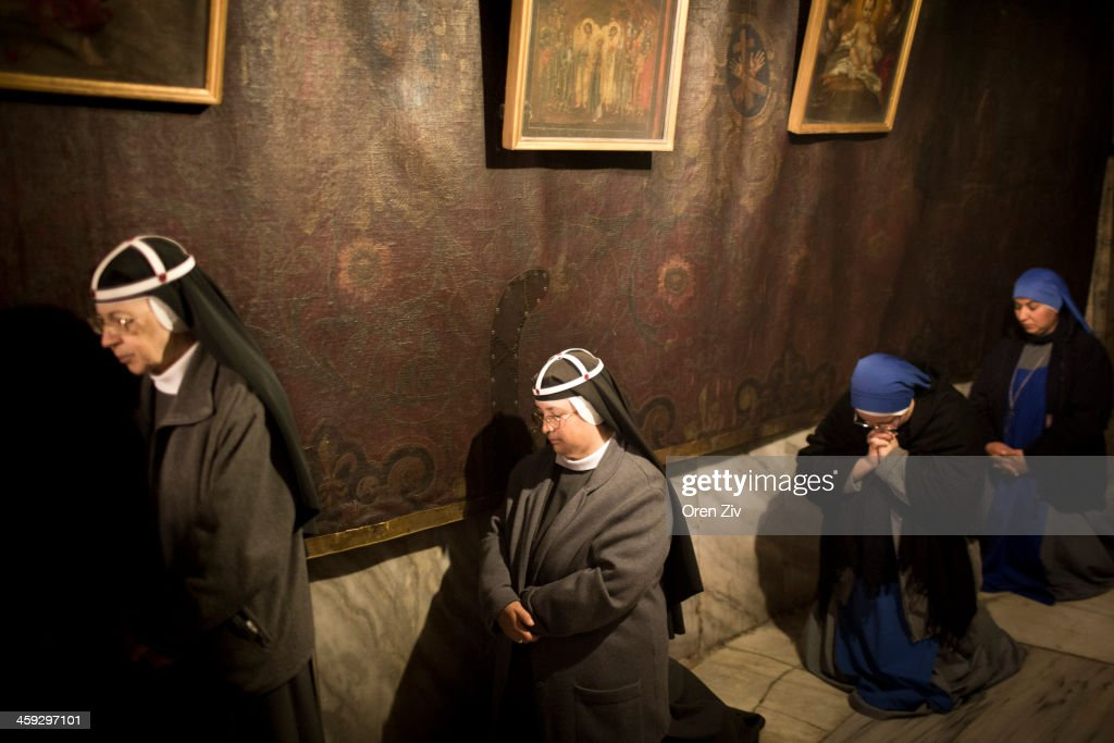 Christian nuns and worshippers pray at the Grotto at the Church of the Nativity on December 25, 2013 in Bethlehem, West Bank. Every Christmas pilgrims travel to the church where a gold star embedded in the floor marks the spot where Jesus was believed to have been born.