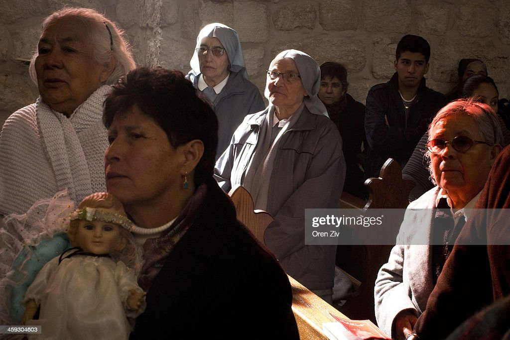 Christian nuns and worshippers sing during a Christmas mass at the Church of the Nativity on December 25, 2013 in Bethlehem, West Bank. Every Christmas pilgrims travel to the church where a gold star embedded in the floor marks the spot where Jesus was believed to have been born.